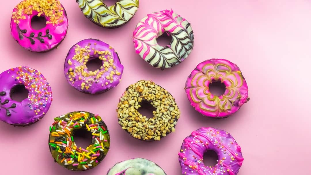 A variety of colorful donut with many different toppings