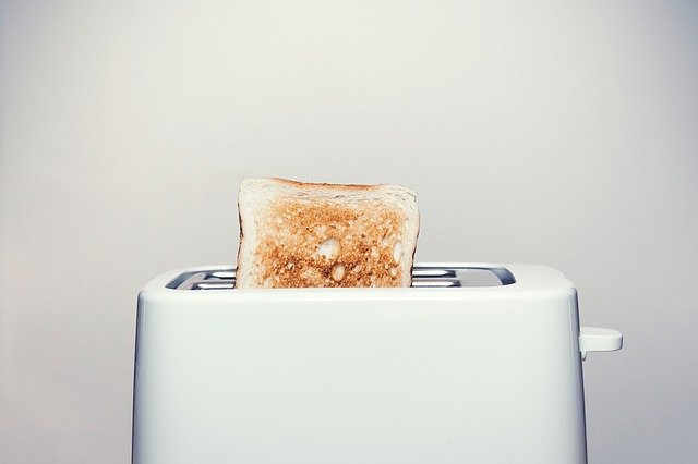 A toaster sitting next to a cup of coffee